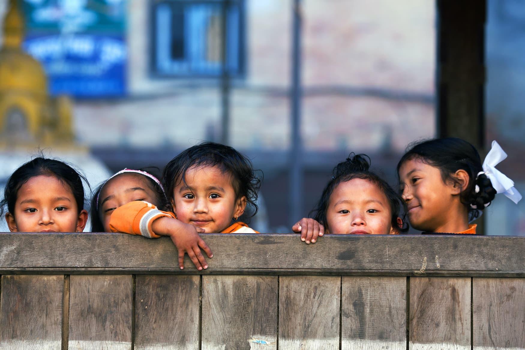 Mädchen in Schule in Nepal lächeln schüchtern in die Kamera und verstecken sich hinter Zaun