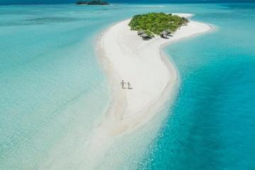 Pärchen spaziert über kleine Privatinsel in den Malediven. Dort versprechen die Resorts Luxus pur.