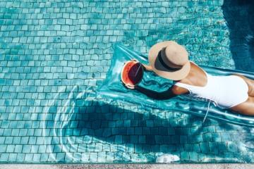 Frau in weißem Badeanzug liegt auf Luftmatratze in Hotelpool und isst Wassermelone