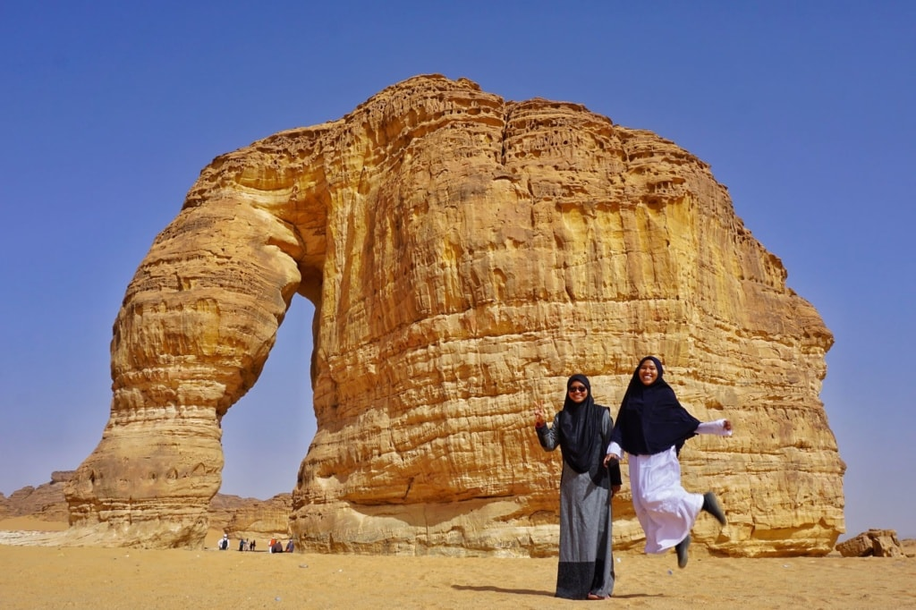 Zwei Frauen posieren vor einem Felsen in Saudi-Arabien