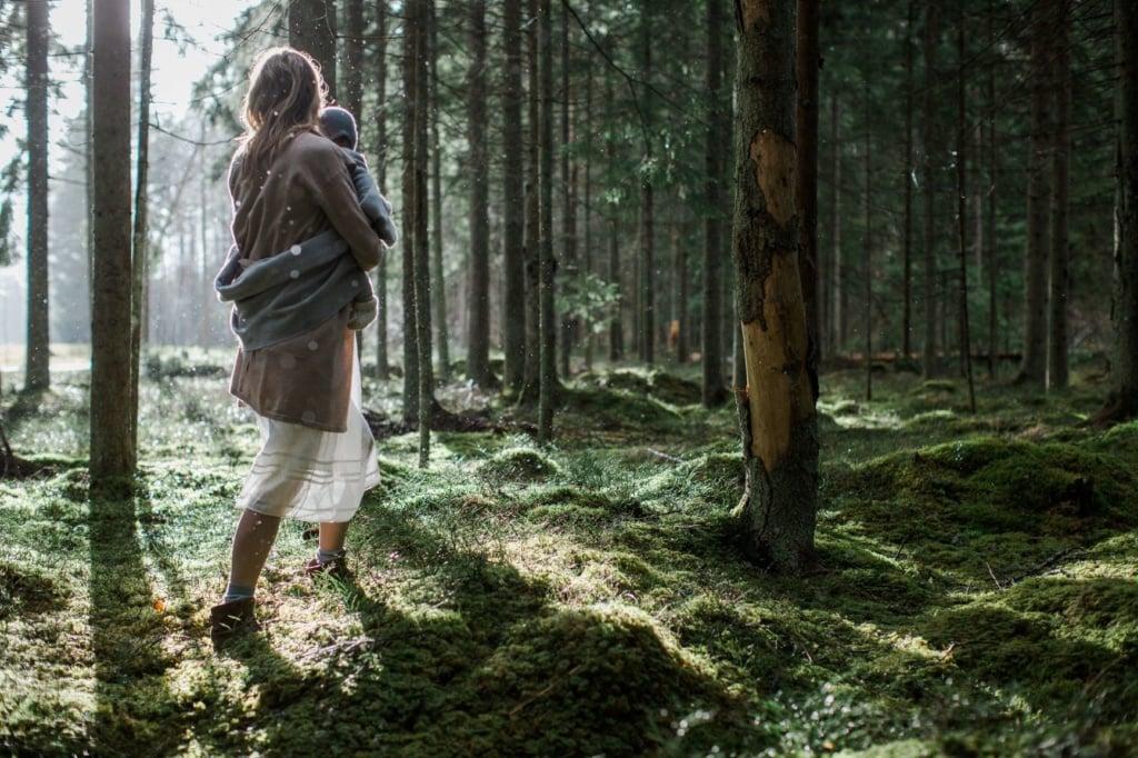 Frau mit Baby in Arm in Estlands Wald