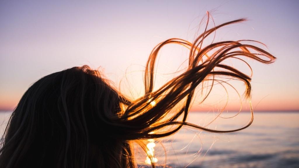 Haare einer Frau am Meer wehen im Wind