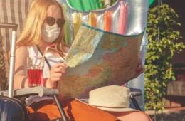 Frau im Liegestuhl mit Corona-Mund-Nasen-Maske und einer Landkarte in der Hand