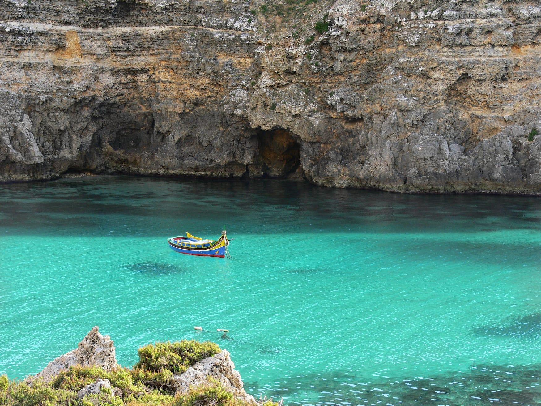 """Buntes maltesisches Fischerboot """"Iuzzu"""" schwimmt vor Anker im kristallklaren türkisfarbenen Wasser in einer Bucht der Insel Gozo"""