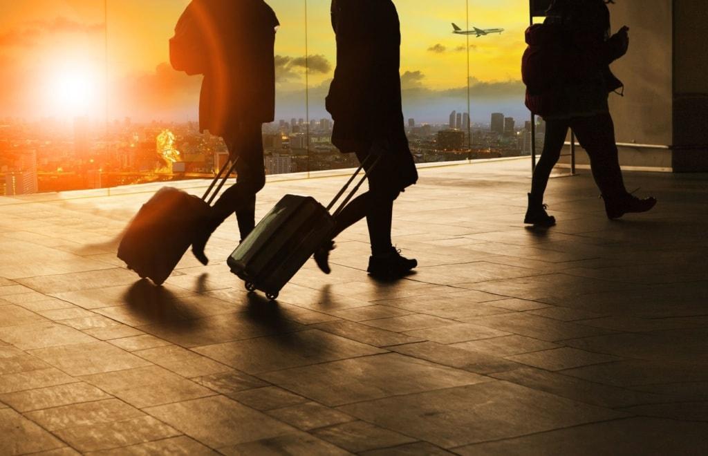 Flugreisende mit Rollkoffer bei Ankunft im Flughafen