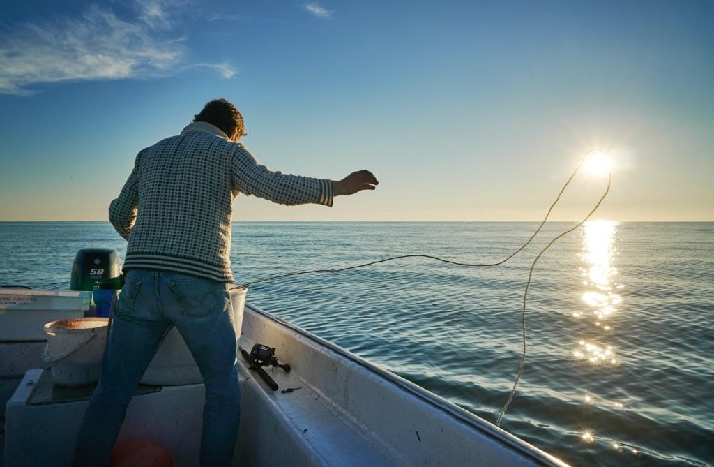 Fischer wirft Netz von seinem Boot bei Sonnenuntergang in Norwegen