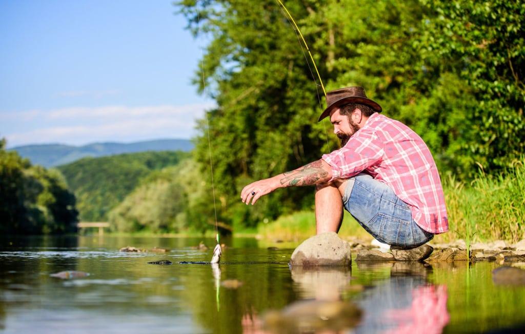 Fliegenfischer zieht seinen Fang aus dem wasser