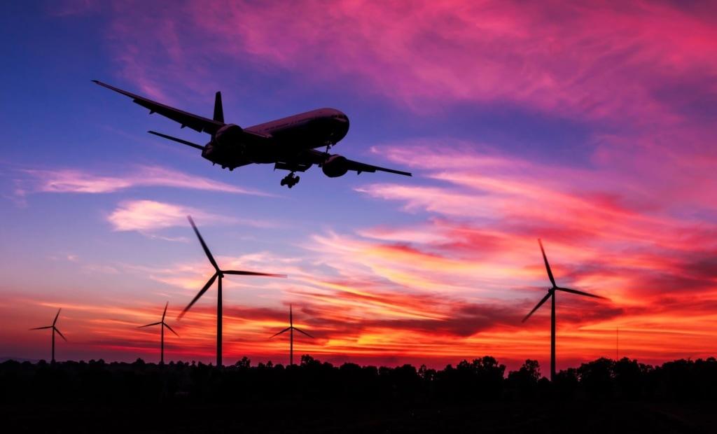 Flugzeug landet, im Hintergrund Windräder