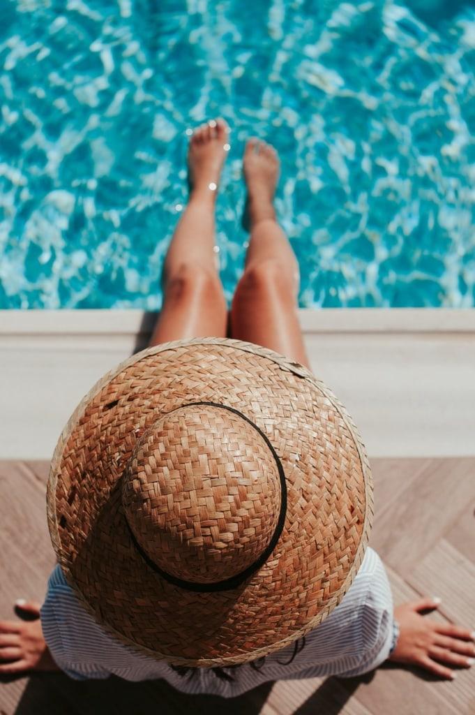 Frau mit Sonnenhut sitzt am Pool und hält ihre Füße ins Wasser