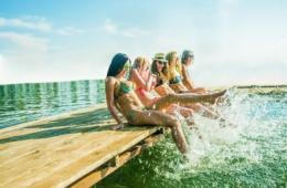Hitzewelle: Fünf junge attraktive Frauen sitzen auf einem Holzsteg und planschen mit Füßen im Wasser