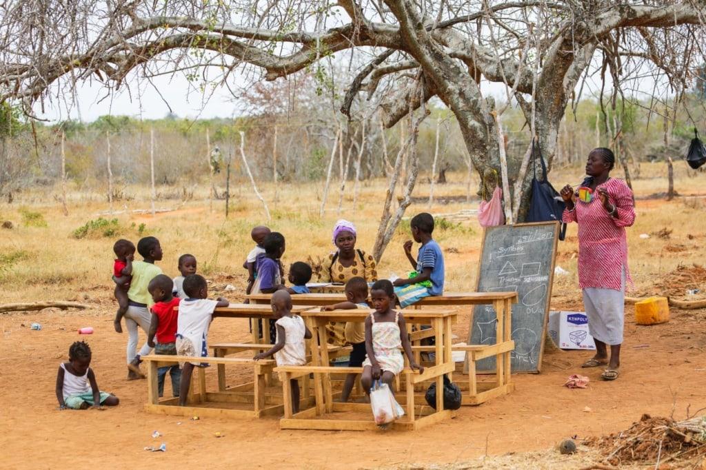 Grundschul-Kinder sitzen im Freien in Kenia
