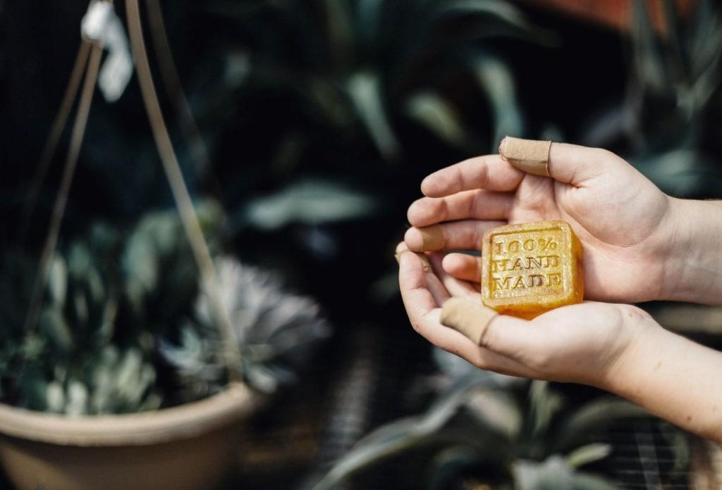 Person hält Seife mit Aufschrift 100% handmade in der Hand
