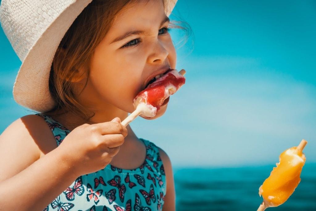 Mädchen mit Sonnenhut isst zwei Eis