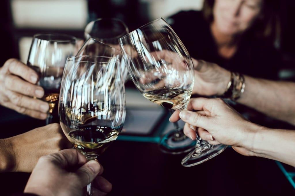 Personen stoßen mit Weißwein an