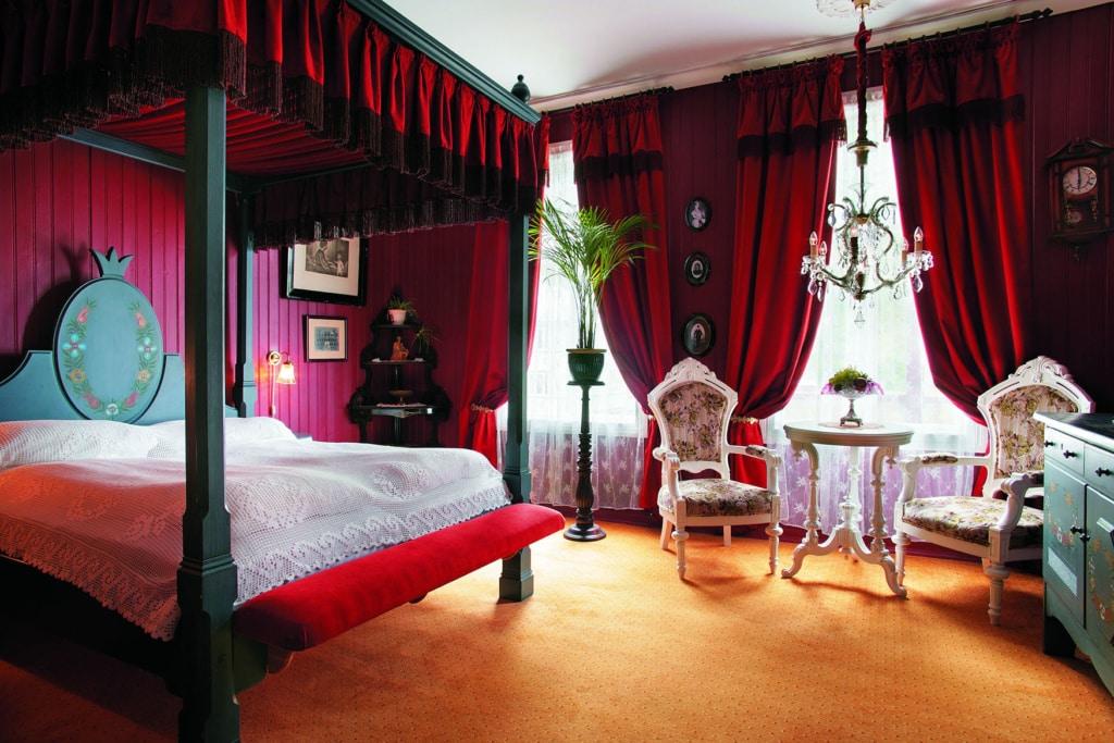 Ein Hotelzimmer mit roten Samtvorhängen, Himmelbett und Antiquitäten