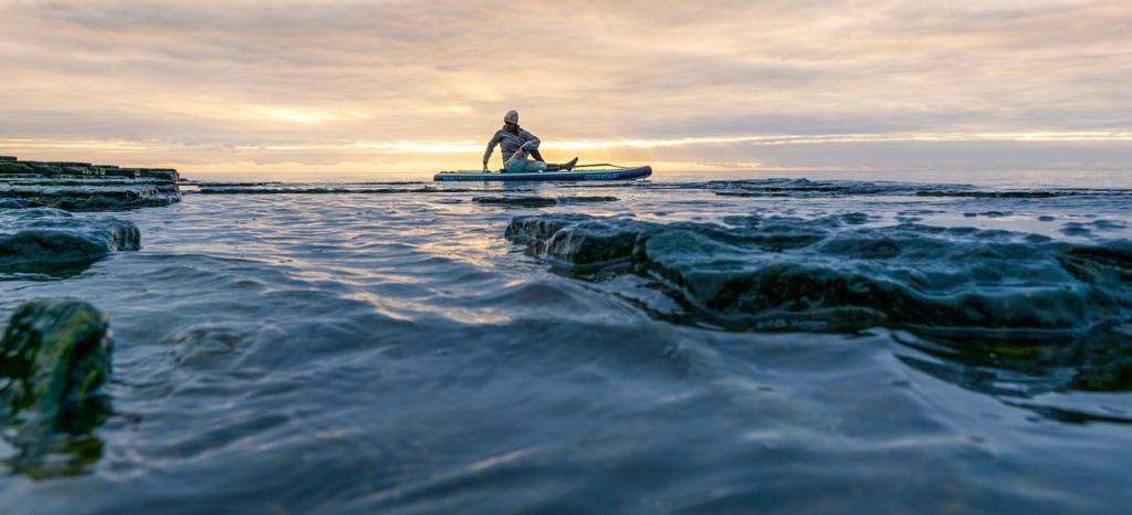 Mann sitzt auf einem SUP Board auf dem Meer