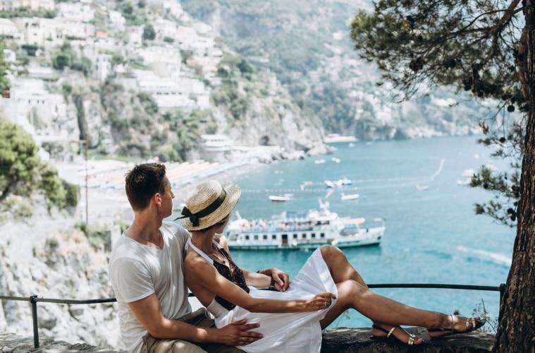 Paar sitzt auf einer Mauer mit Blick auf Positano