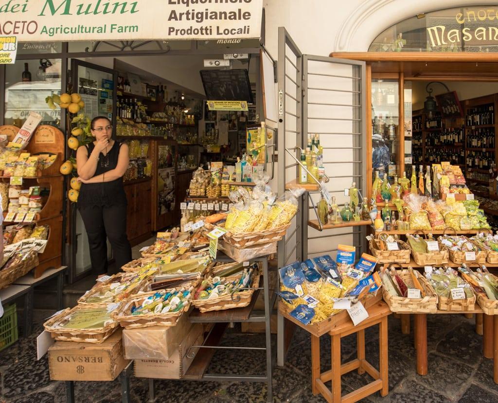 Frau steht vor ihrem Lebensmittelladen, wo sie Pasta und Obst verkauft
