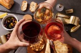 Drei Personen stoßen mit je einem Glas Weiß-, Rot- und Rosewein an