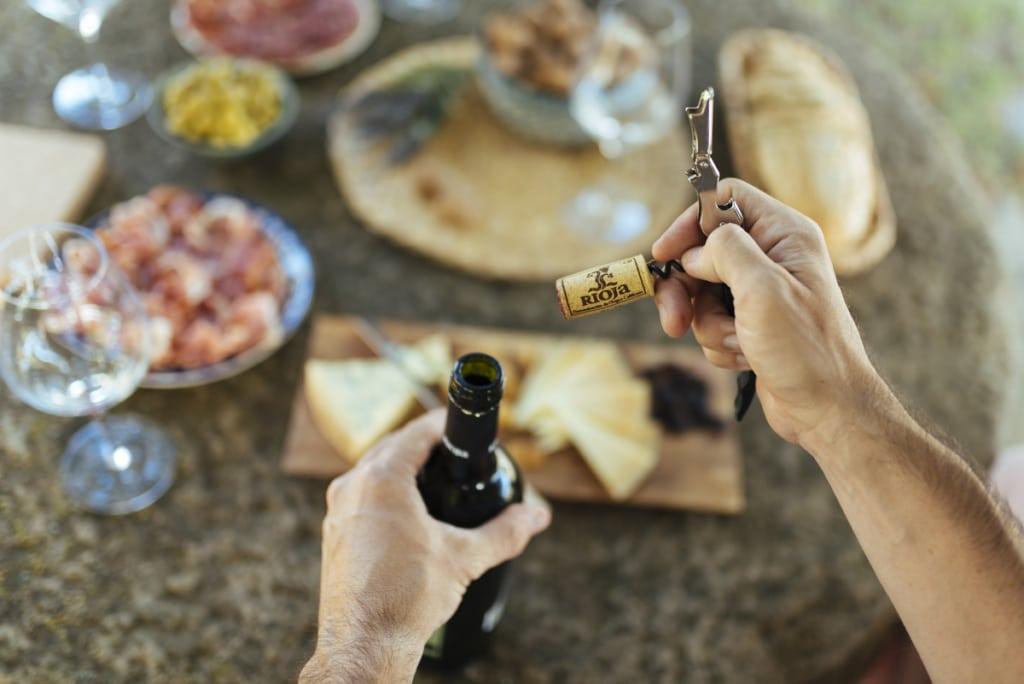 Hand öffnet Rioja-Weinflasche