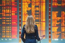 Elegant gekleidete Frau steht am Flughafen vor einer riesigen Anzeigetafel