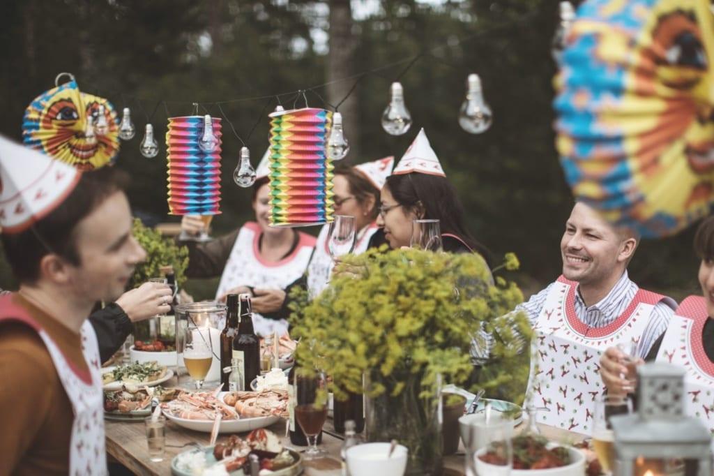 Schweden sitzen am Tisch und feiern das Krebsfest
