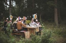 Schweden sitzen im Wald an einem Holztisch und feiern das Krebsfest