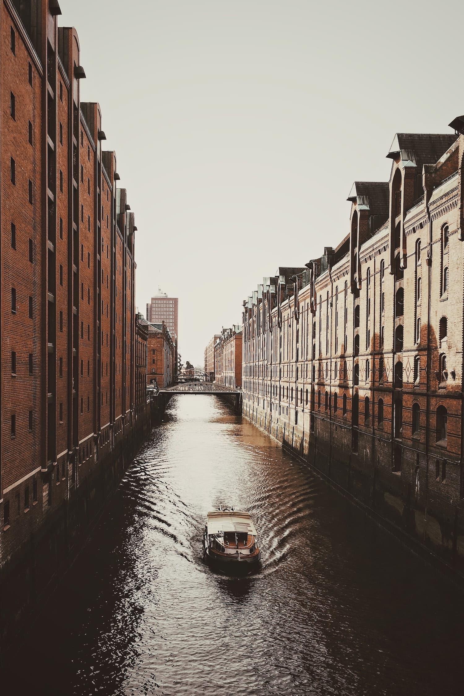 Boot fährt bei Abendstimmung durch die Speicherstadt in Hamburg