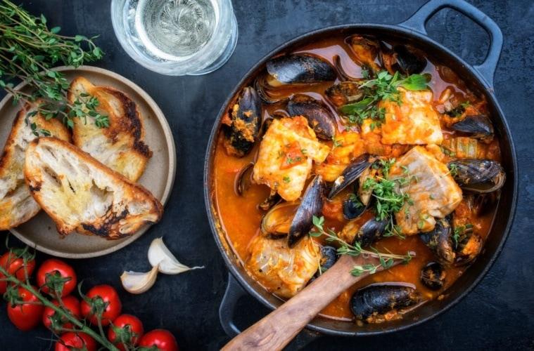 Traditioneller französischer Fischeintopf mit Muscheln und Knoblauchbaguette