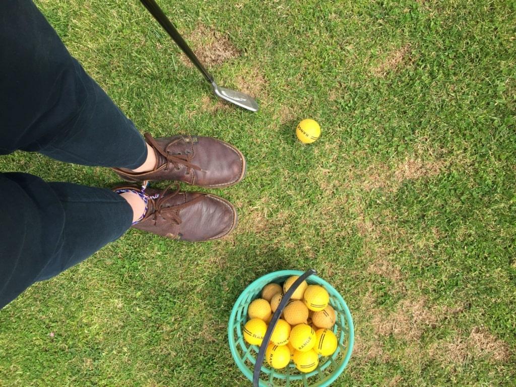 Eimer mit Golfbällen steht auf Wiese