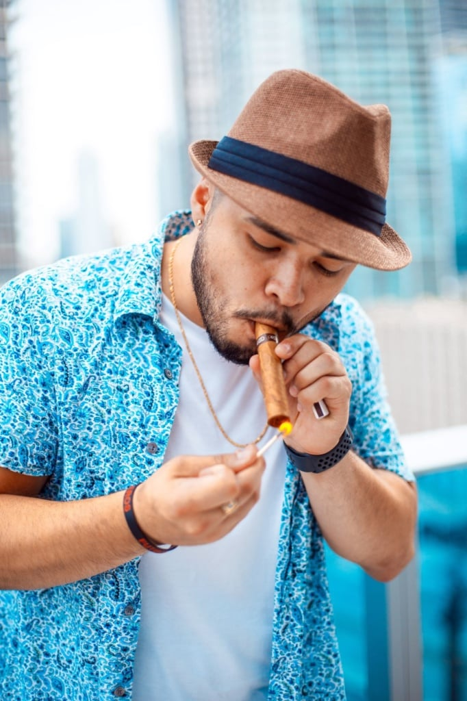Latino mit Hut zündet sich Zigarre an