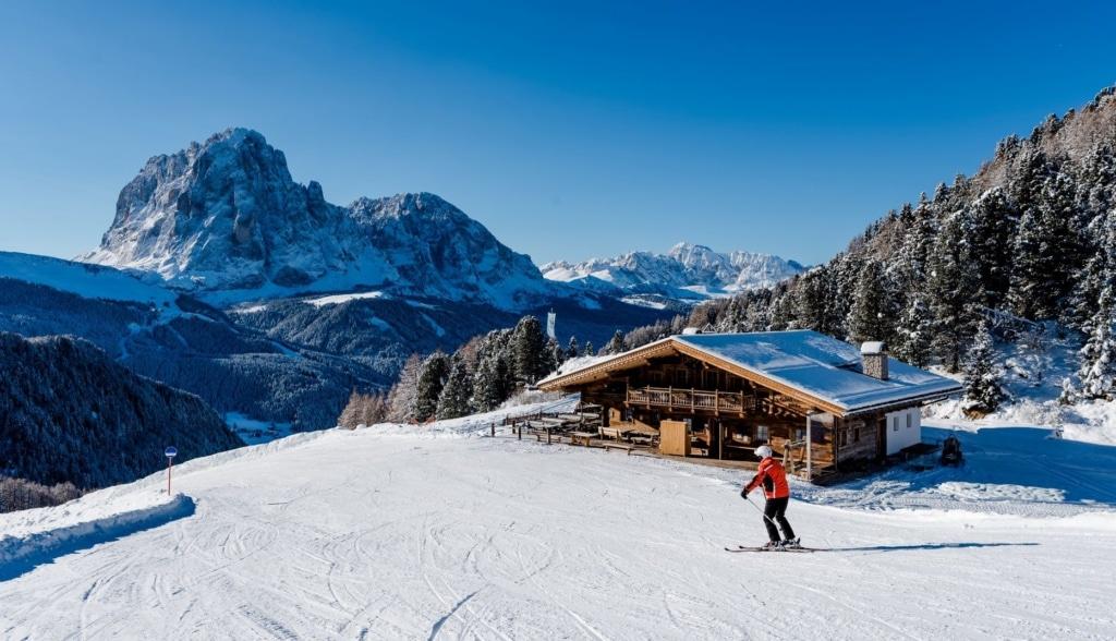 Skiurlaub in diesem Corona-Winter: Skifahrer fährt an Hütte im Grödental vorbei