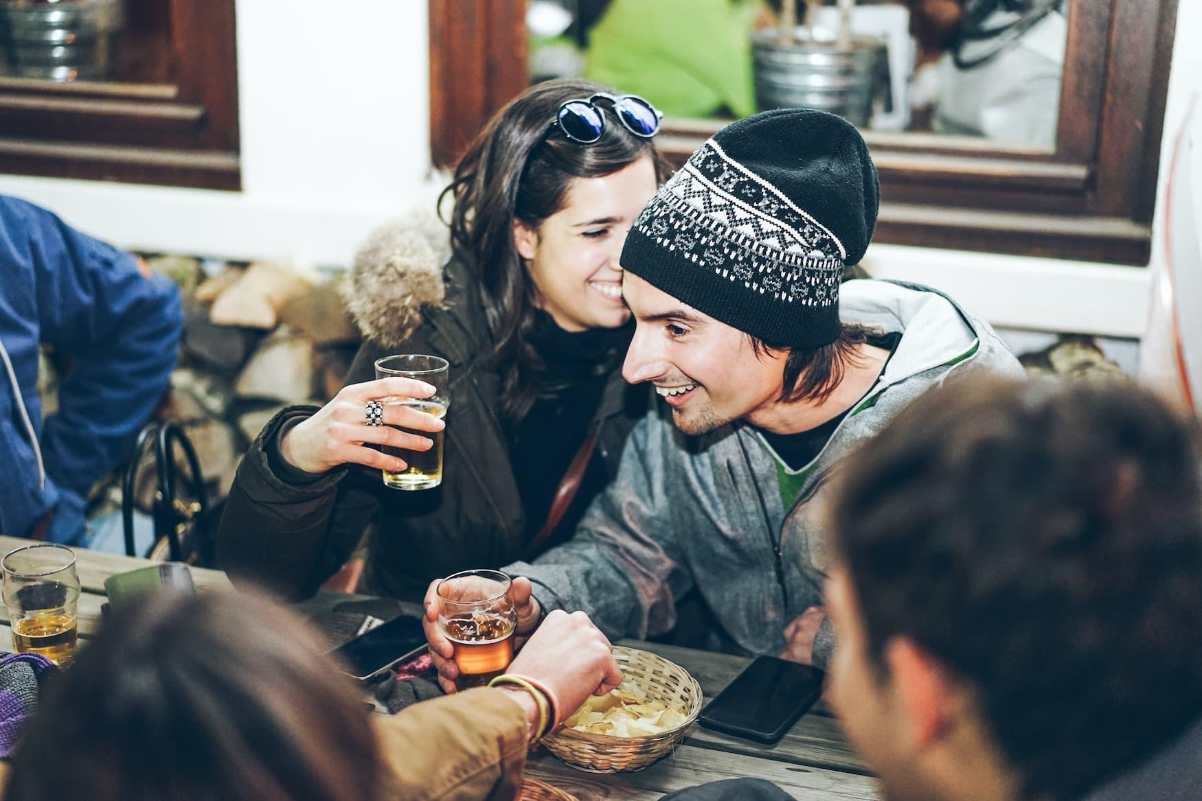 Freunde sitzen gemeinsam beim Apres Ski und trinken Bier