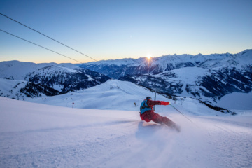 Ski-Fahrer auf der Winterskipiste in Österreich. Farbiger Sonnenaufgang im Hintergrund.