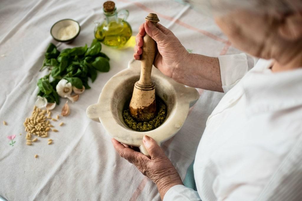 Eine dame bereitet ein grünes Pesto in einem Mörser zu