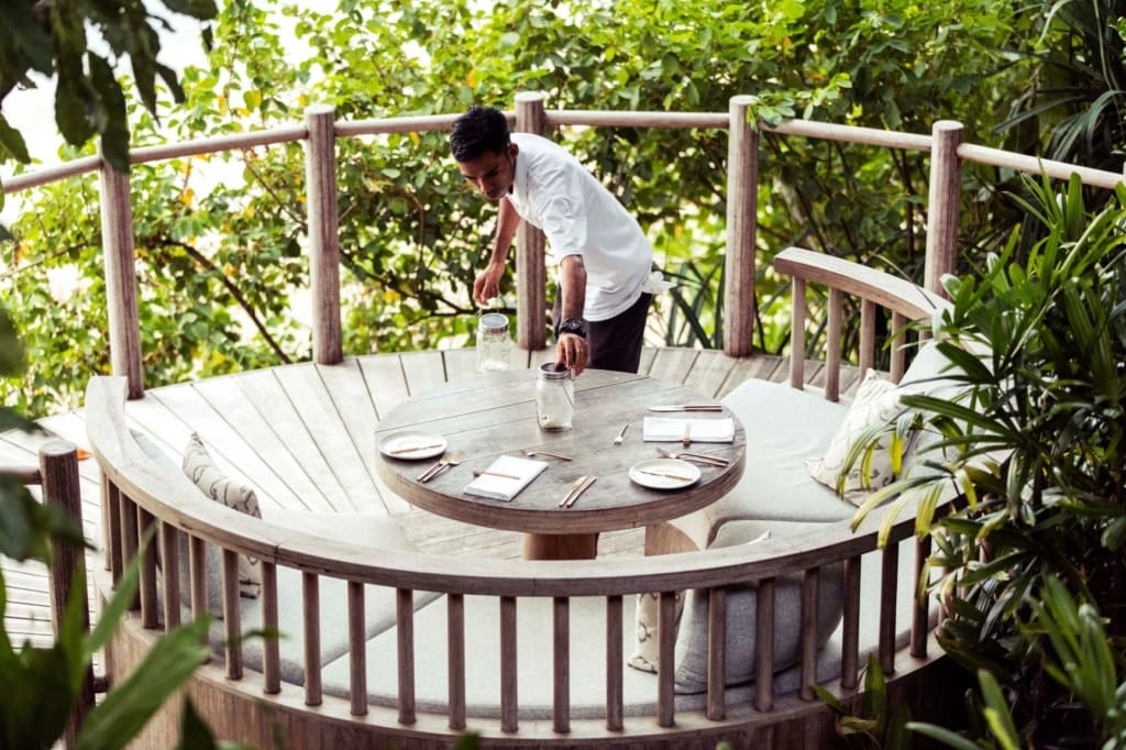 Cempedak Island: Kellner bereitet Tisch fürs Abendessen vor