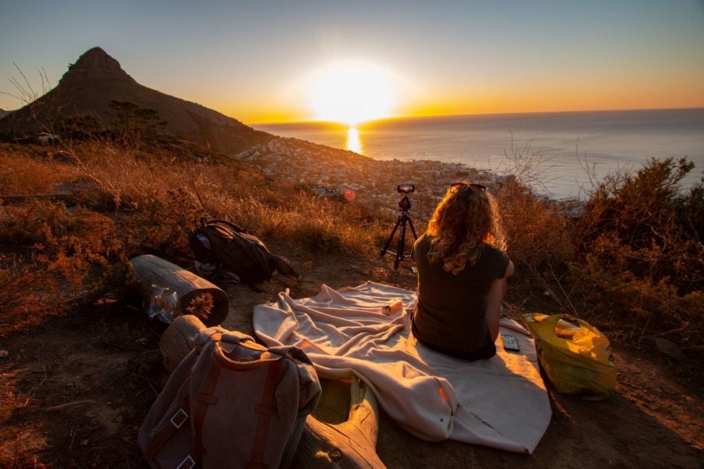 Frau sitzt auf Decke am Meer und beobachtet Sonnenuntergang