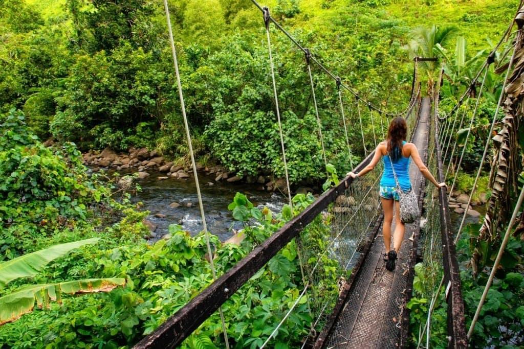 Junge Frau, die auf dem Lavena Coastal Walk über eine Hängebrücke über den Bach Wainibau auf Taveuni Island, Fidschi, geht.