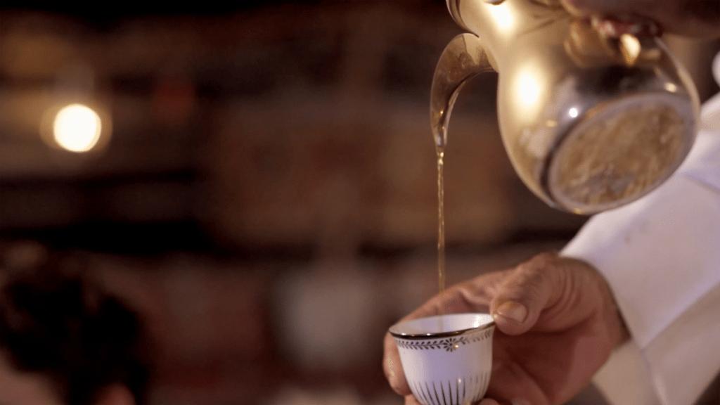 Mann schenkt arabischen Kaffee aus einer Dallah ein