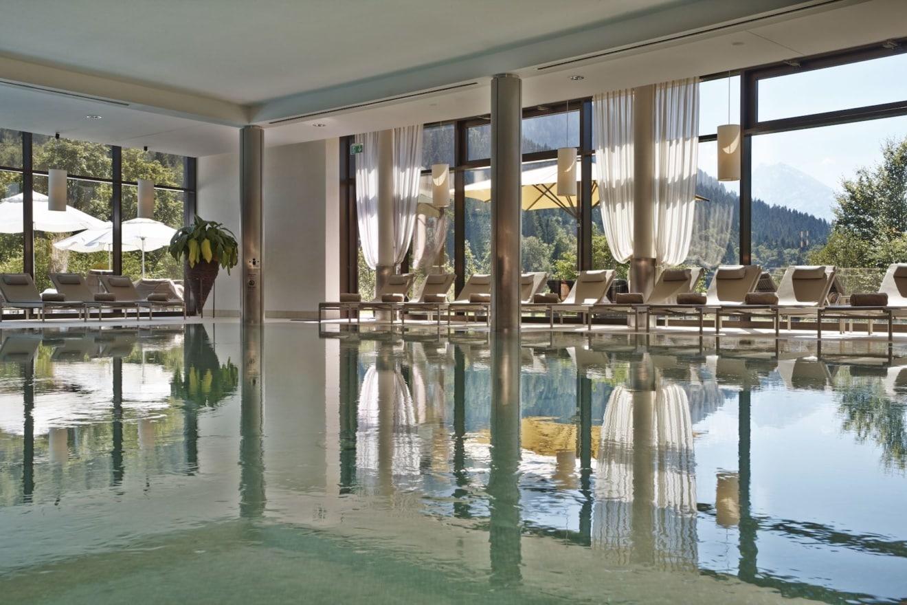Im Spa des Kempinski Hotels Berchtesgaden lässt es sich hervorragend im Innenpool mit Bergkulisse entspannen.