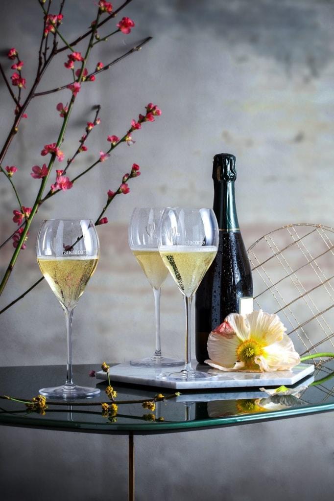 Glastisch mit Flasche Schaumwein und drei gefüllten Gläsern