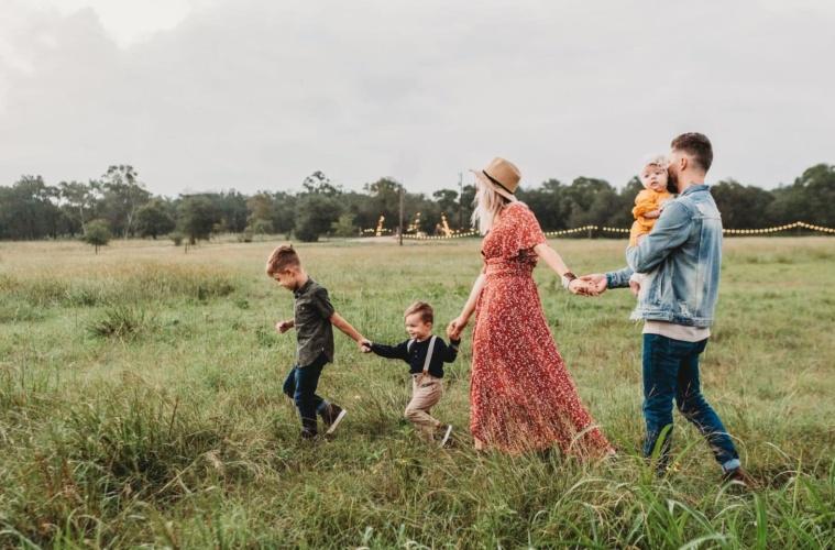 Fünfköpfige Familie geht über Wiese