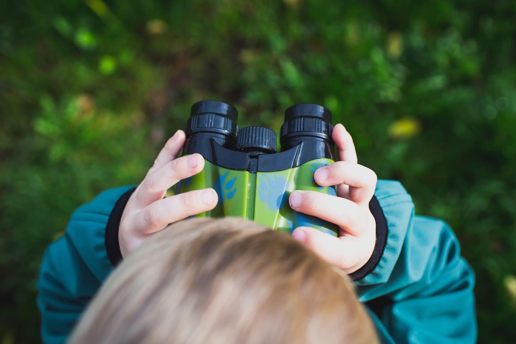 Junge mit Fernglas geht auf Safari in Deutschland
