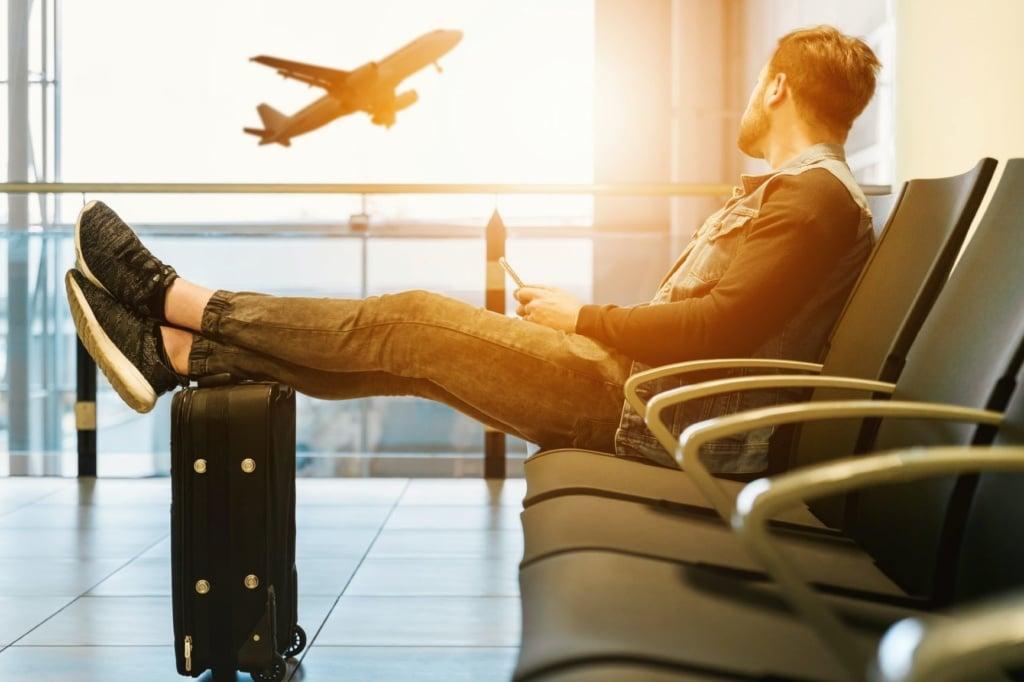 Junger Mann sitzt mit Koffer im Flughafen, im Hintergrund hebt Flugzeug ab
