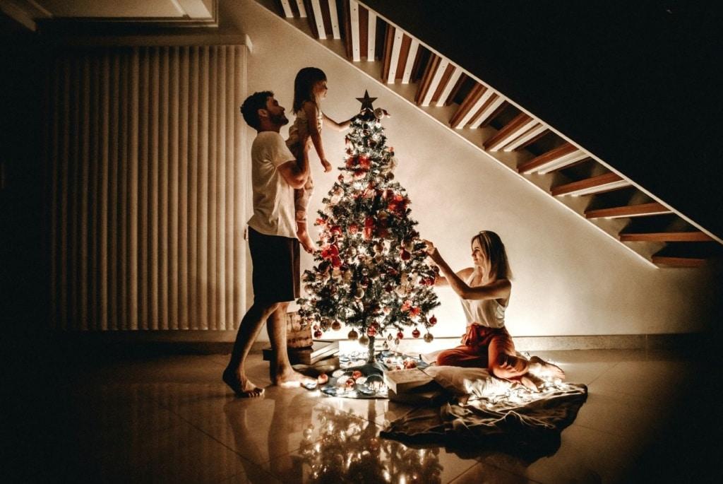 Mann, Frau und Kind schmücken Weihnachtsbaum unter Treppe