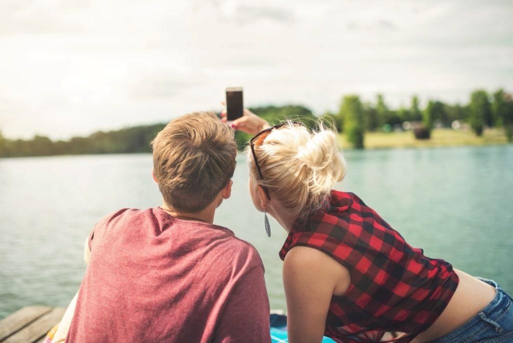 Junger Mann und junge Frau machen am Wasser ein Selfie