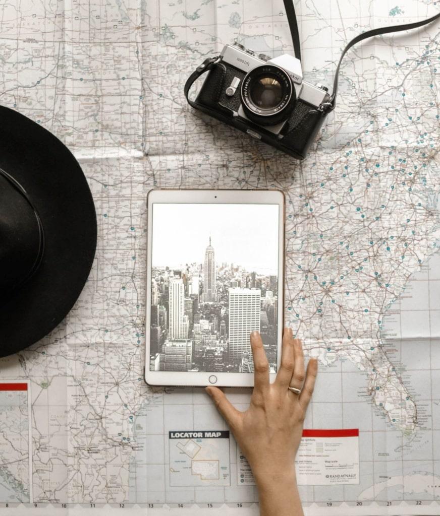 Hand einer Frau, die ein iPad bedient, darunter eine Karte der USA
