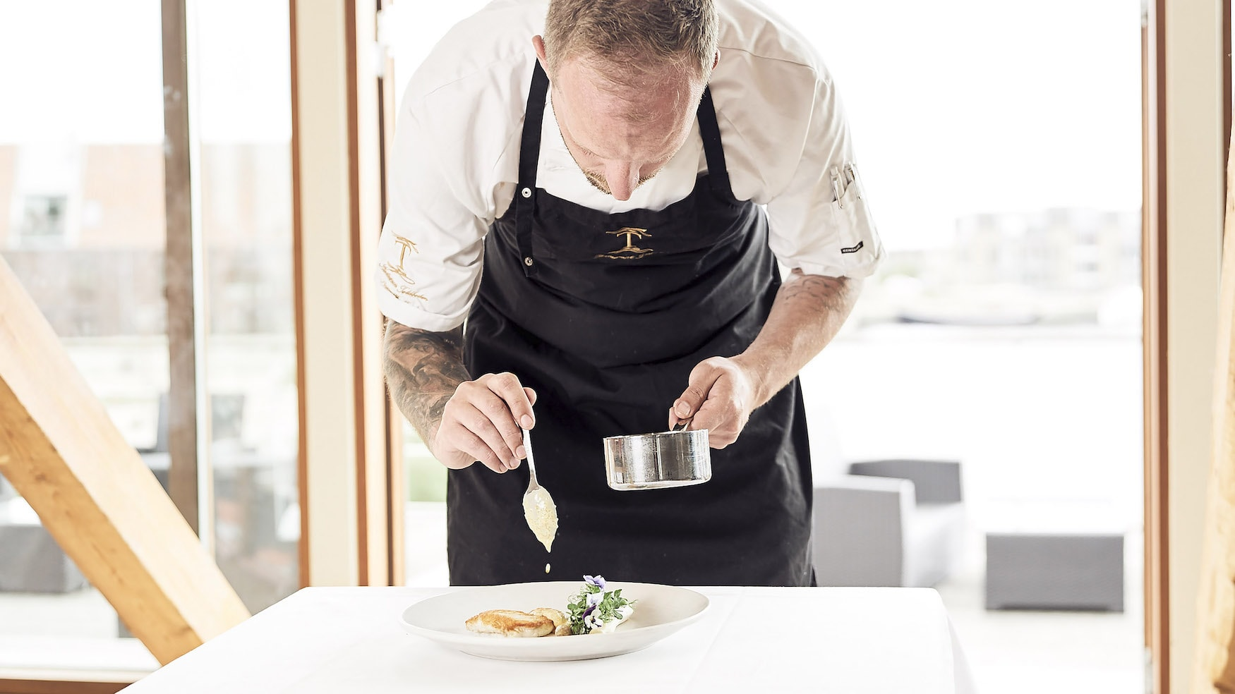 Chefkoch des Restaurants Tolboden richtet einen Teller an.