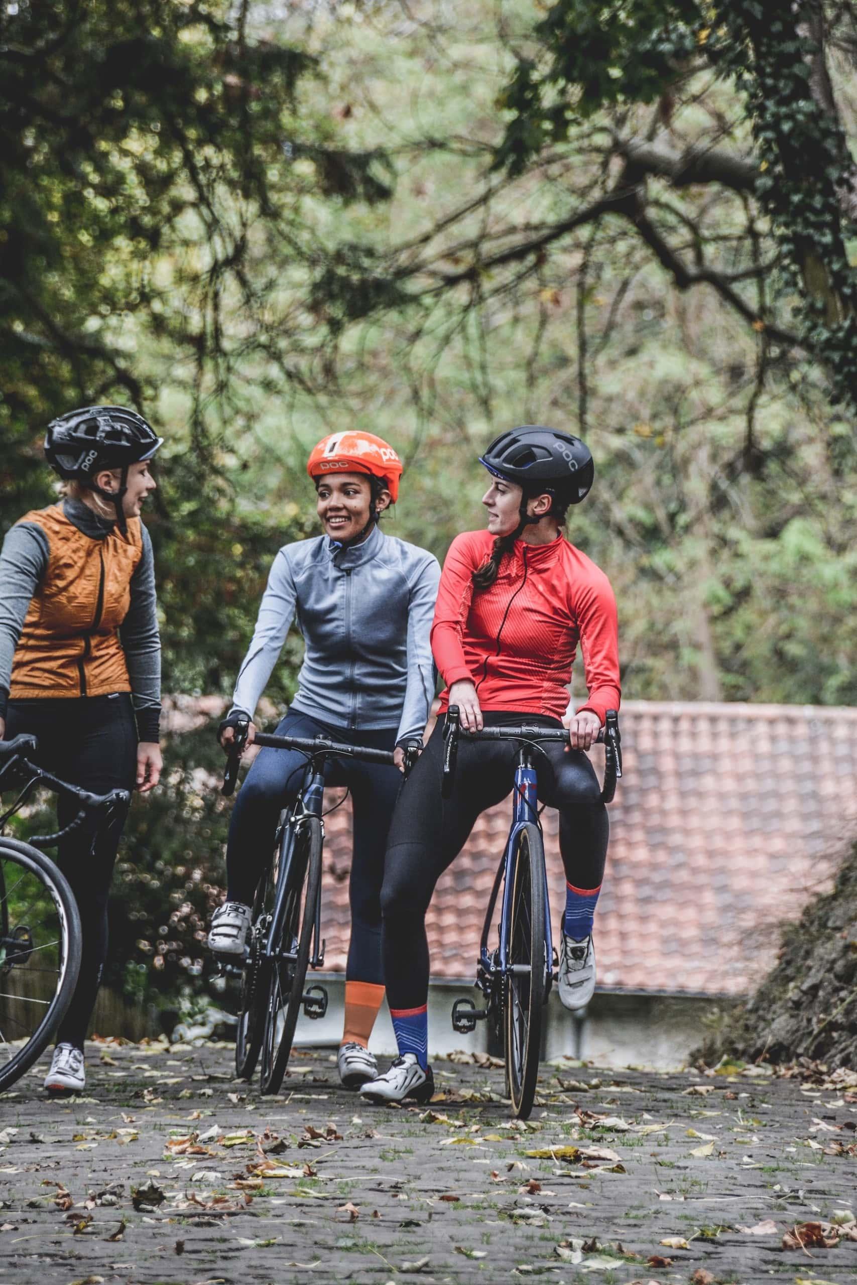 Drei Frauen mit Rennrädern tragen Helm für sicheres Fahrradfahren im Straßenverkehr