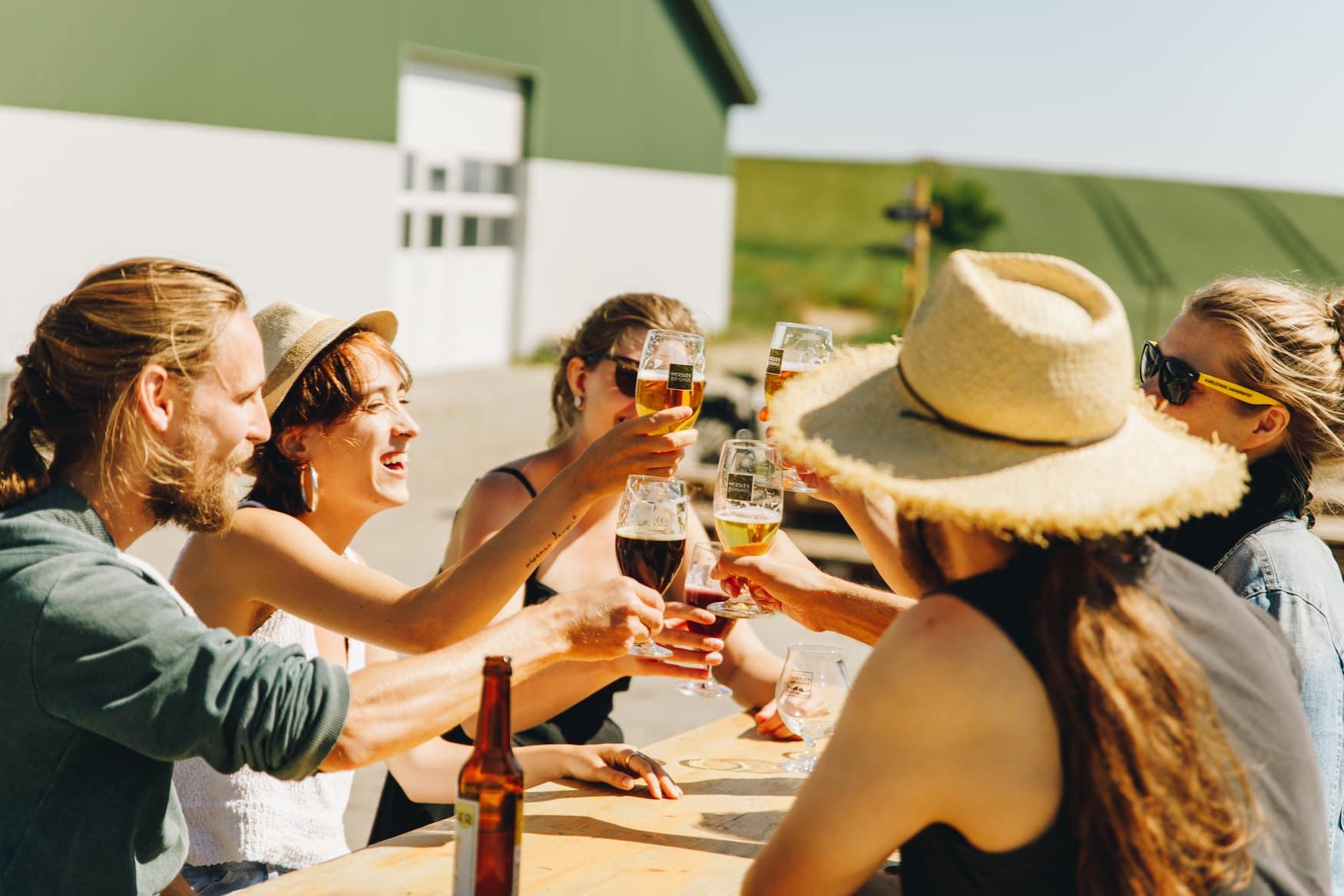 Eine Gruppe von Freunden sitzt vor der Herslev Brauerei und prostet sich zu